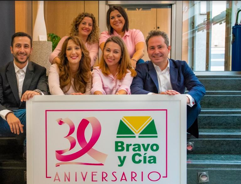 Equipo de Seguros Bravo con un cartel del 30 aniversario
